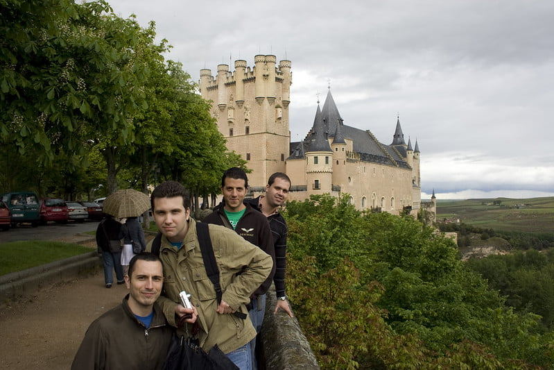 A group of four tourists taking picture in front of the Segovia castle on a cloudy day.