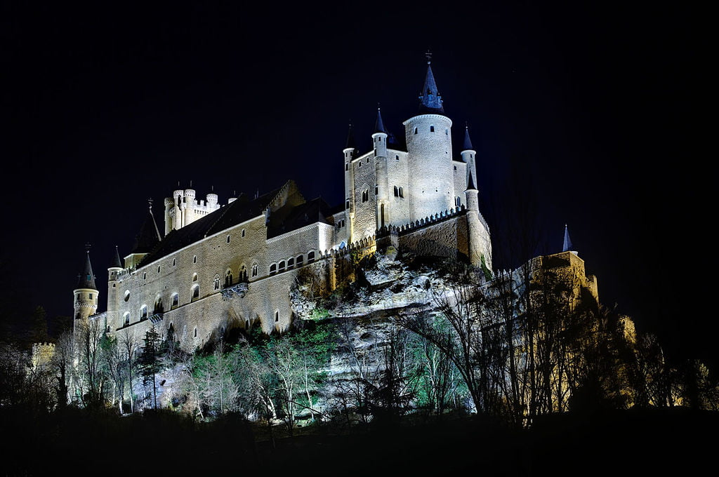 Alcazar of Segovia at the night time shot from below. The castle and the granite hill it stands on are beautifully enlightened.
