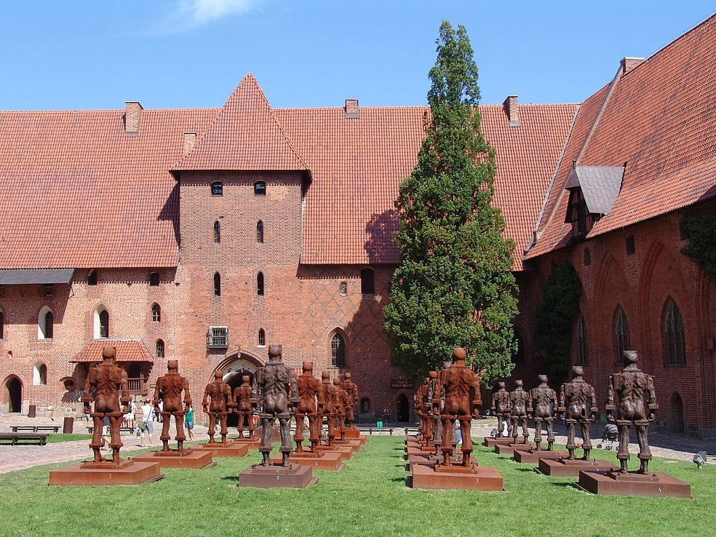 Courtyard of Malbork Castle with multiple metal sculptures of the knights of Teutonic Order