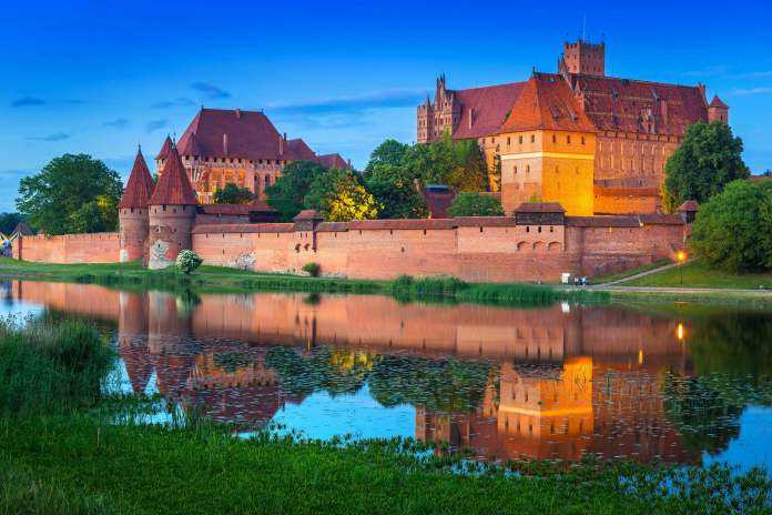 Malbork castle at dusk from the other side of the river.