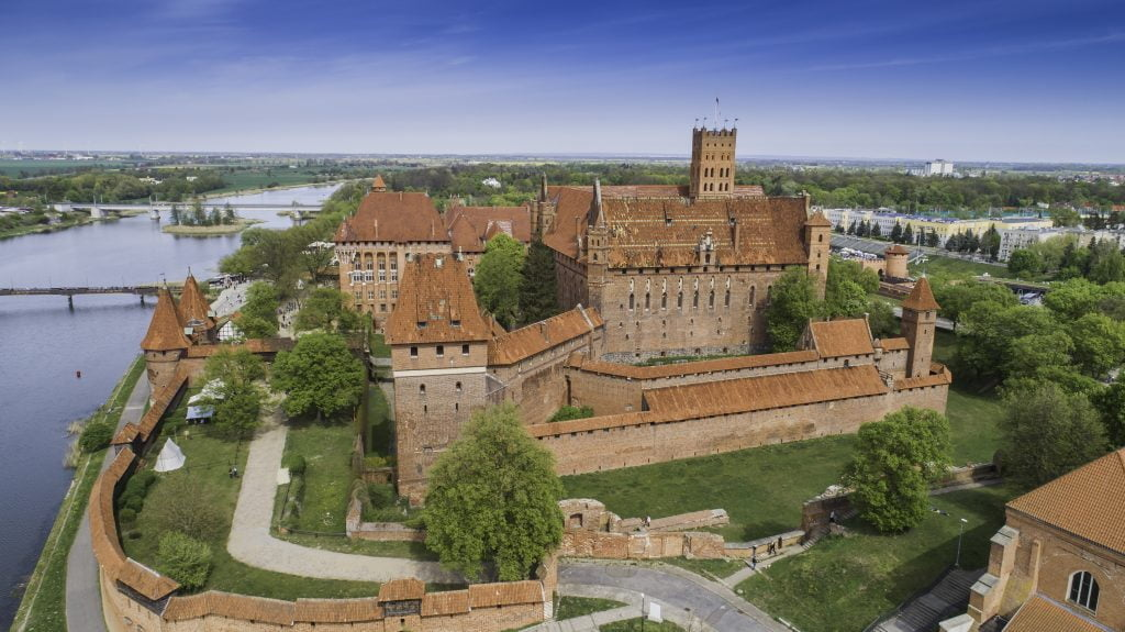 aerial shot of malbork castle from a side view