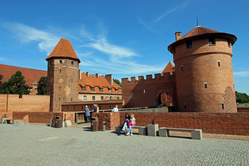 Two Malbork castle towers appear infront of each other separate by the bridge with tourists walking