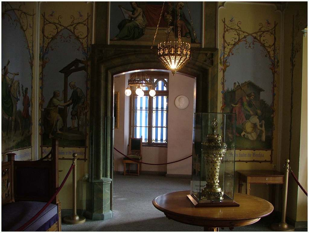 Hohenschwangau Castle sneak peek of its beautiful palace interior with a golden vase and wall paintings.