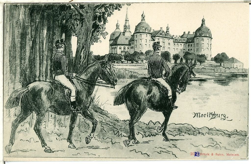A postcard from 1899 with two horsemen and the Moritzburg castle in the background in black and white.