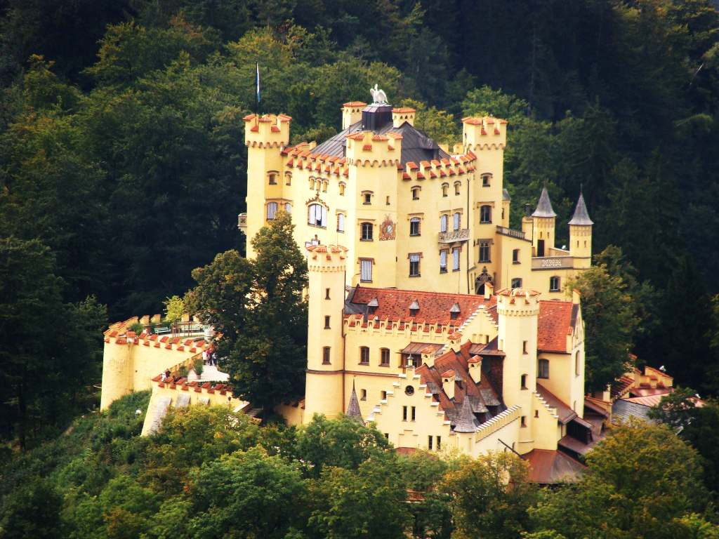 An aerial view of the Hohenschwangau castle with its forestry green surroundings