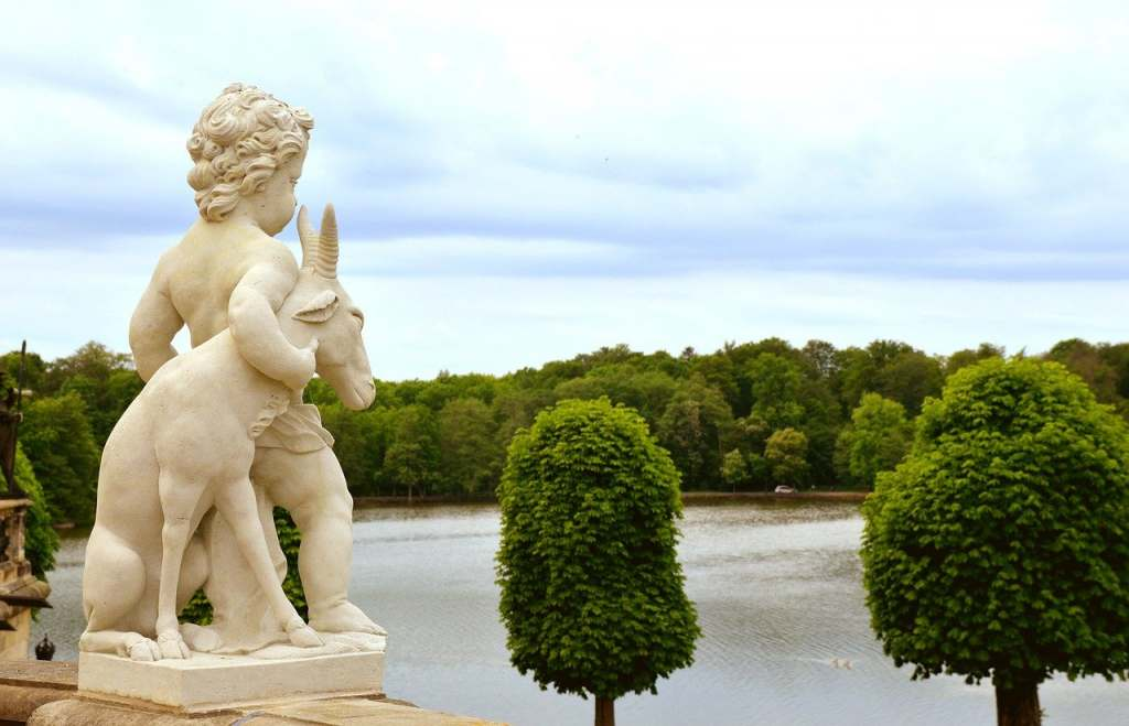 The statue of a boy and a goat looking into the horizon from the balcony of Moritzburg castle with lots of greenery around.