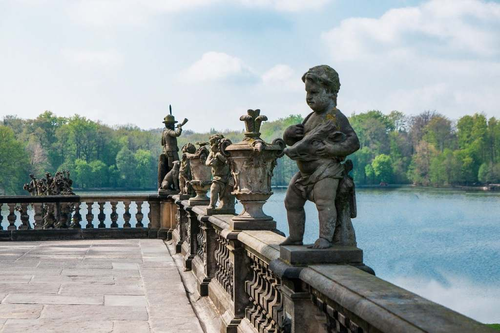 A lineup of statues on the balcony of Moritzburg castle with the lake and trees in the light background.