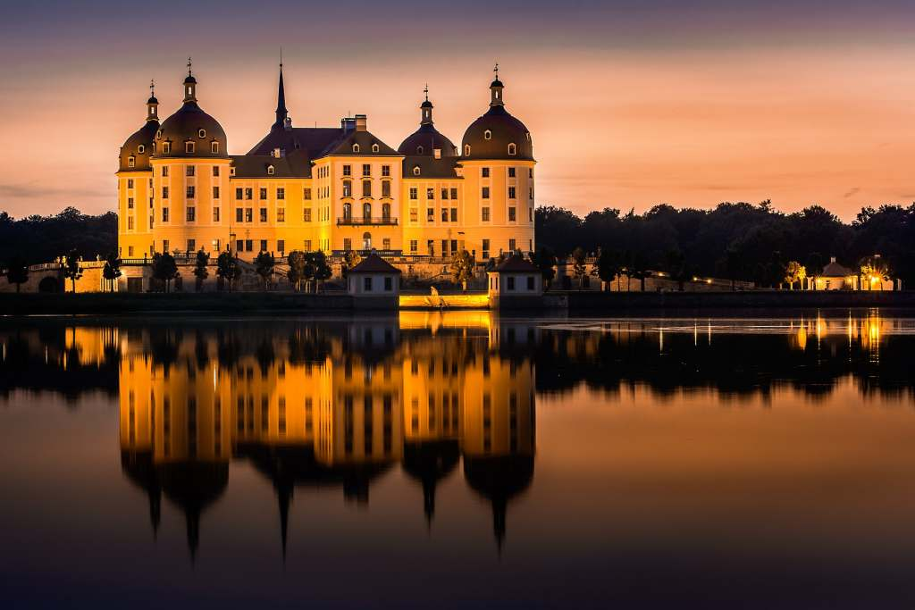 moritzburg castle from a far reflecting on the surface on the lake in the nigh