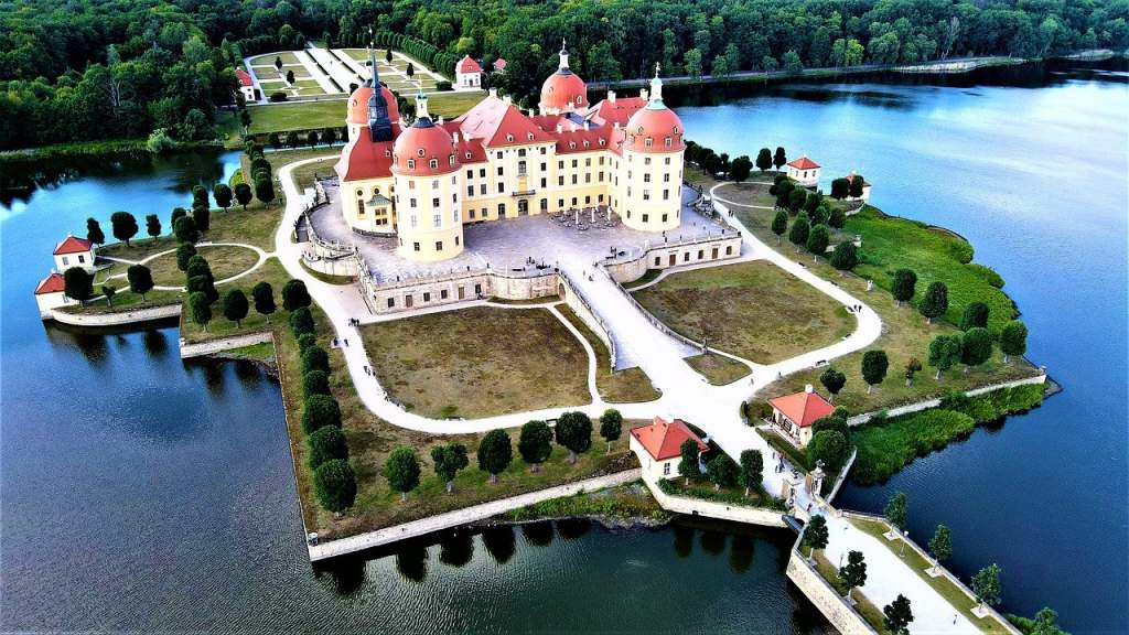 Beautiful aerial drone shot of Moritzburg castle and its perfectly shaped island surrounded by the lake moat, trees and the bridge.