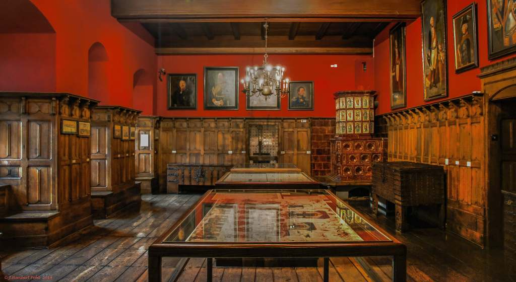 The interior of the Altena Castle museum in front view with red wall and paintings.