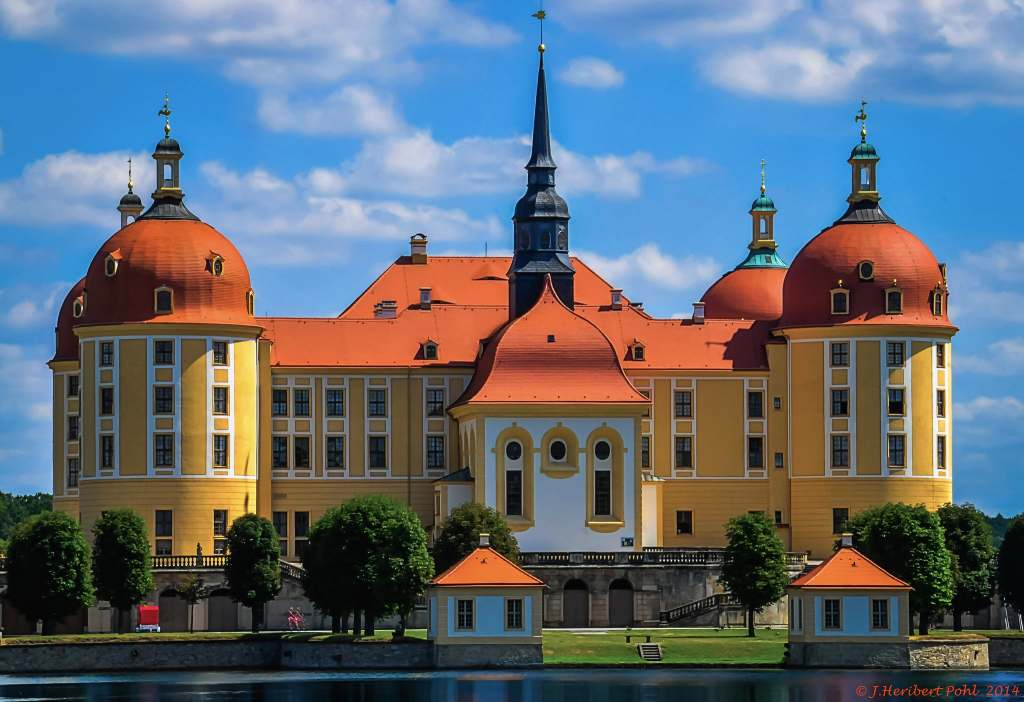 The dramatic baroque-style architecture of the Moritzburg castle with red rooftops in the sunlight.