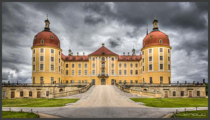 The beautiful, highly symmetrical architecture of the Moritzburg castle with dark clods in the sky.
