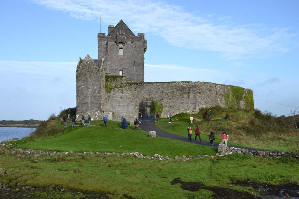 The entrance and stone walls of the Dunguaire castle and tourists on their way inside.