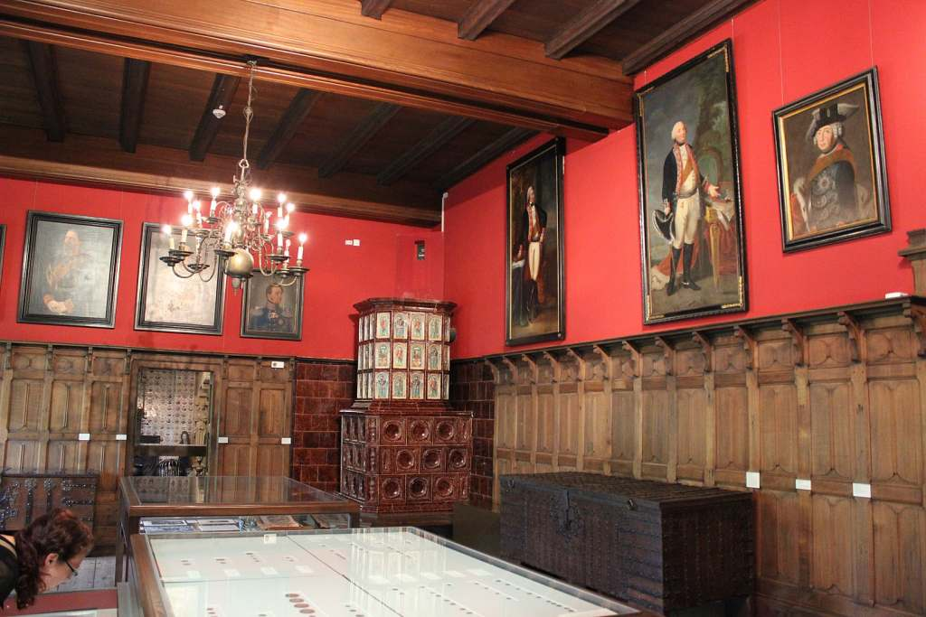 The inside view of one of the museum in Altena Museum with red walls and paintings.