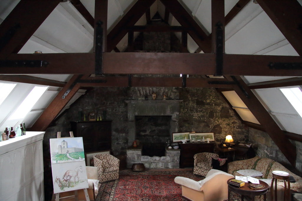 The beautiful cozy attic with chimney, paintings and sofa seats in Dunguaire Castle.