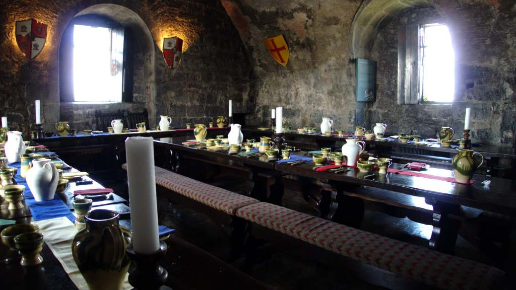 The banquet hall in Dunguaire Castle with candles goblets and porcelain pitchers.