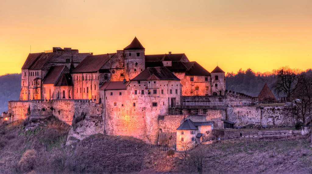 A beautiful view of Burghausen Castle in twilight evening with lights turned on..