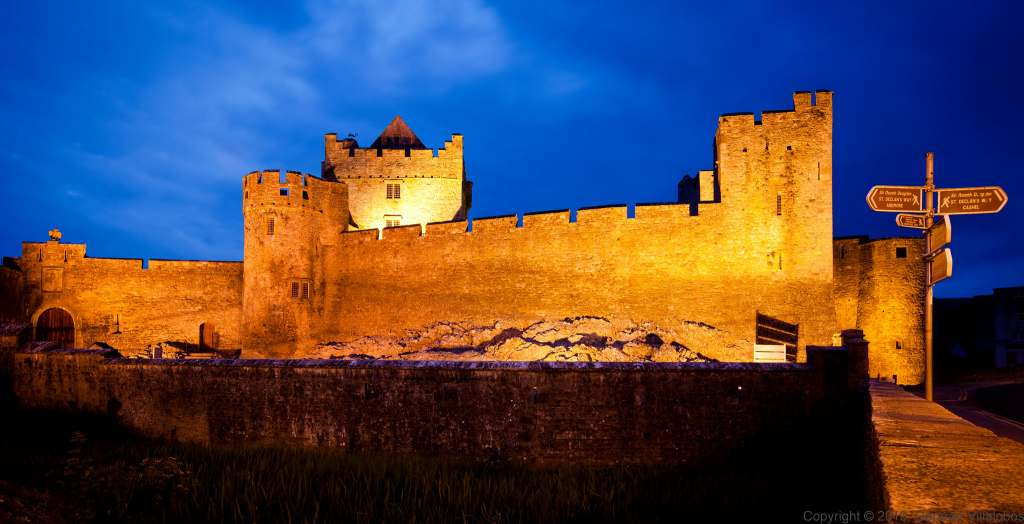 Cahir Castle's main entrance view at night with lights on.
