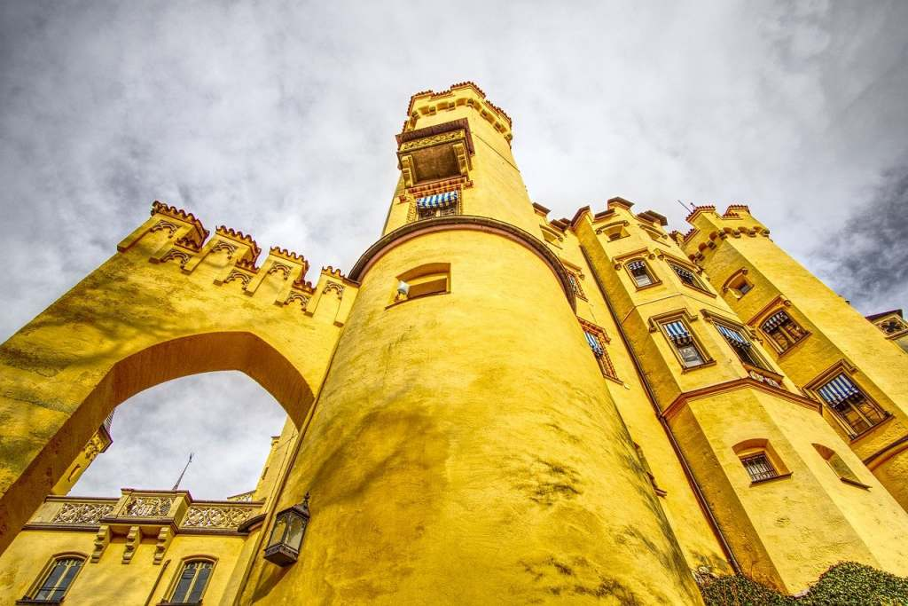 Steep high bright yellow wall of the Hohenschwangau castle from the bottom.