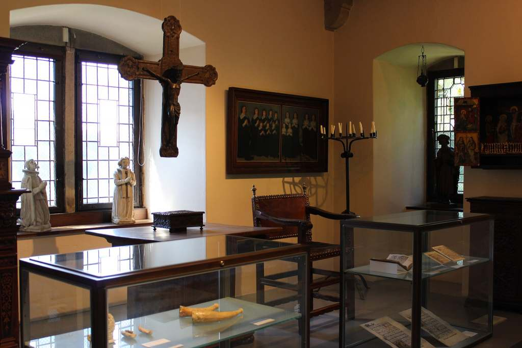 The inside of Altena Castle Museum where you can see a crucifix, books and statutes.