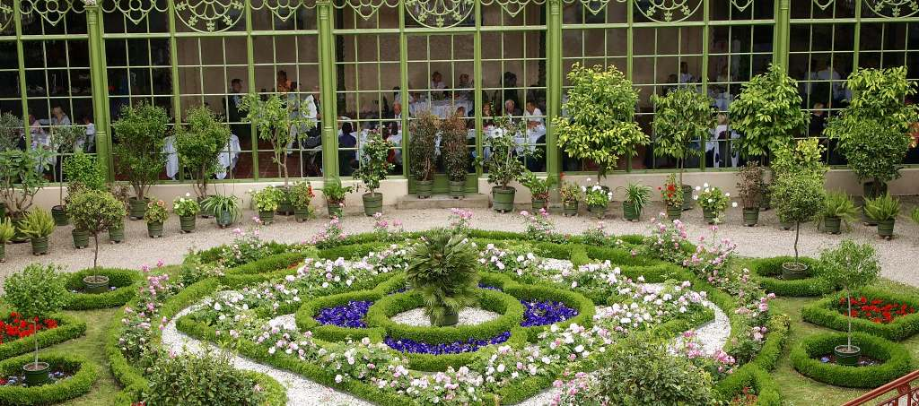 Beautiful pavilion garden of the Schwerin castle with red, purple and white flowers in front of the dining area.