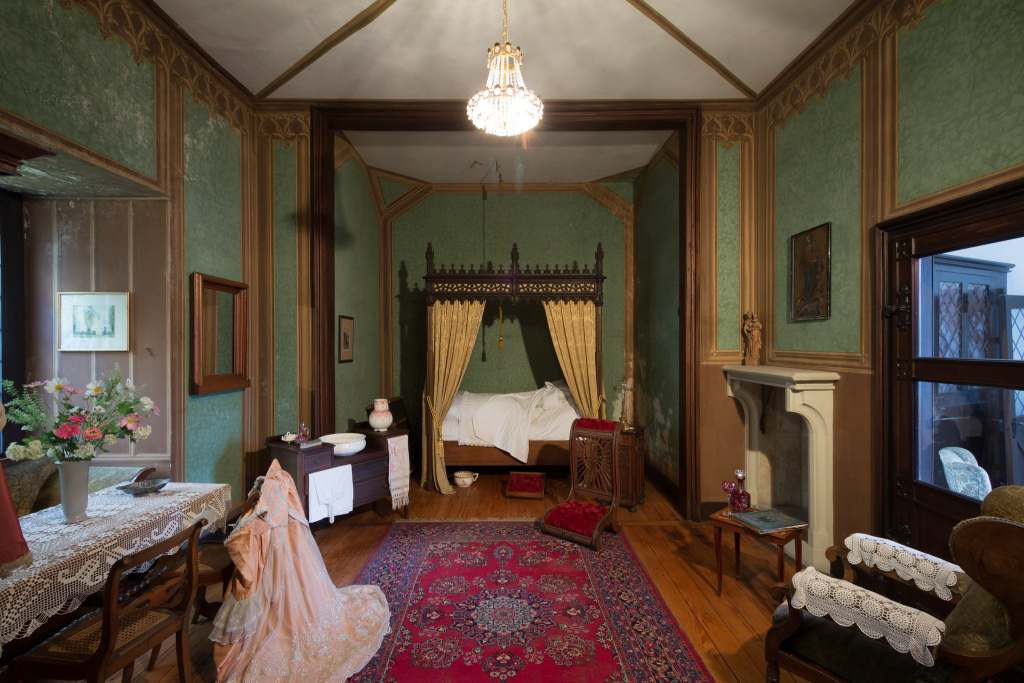 One of the elegant bedrooms at the Rheinstein castle with green wallpaper and a chandelier.