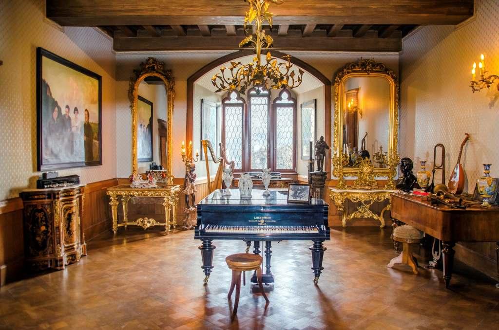 Rheinstein Castle's golden interior with piano display, beautiful chandelier and musical instruments.