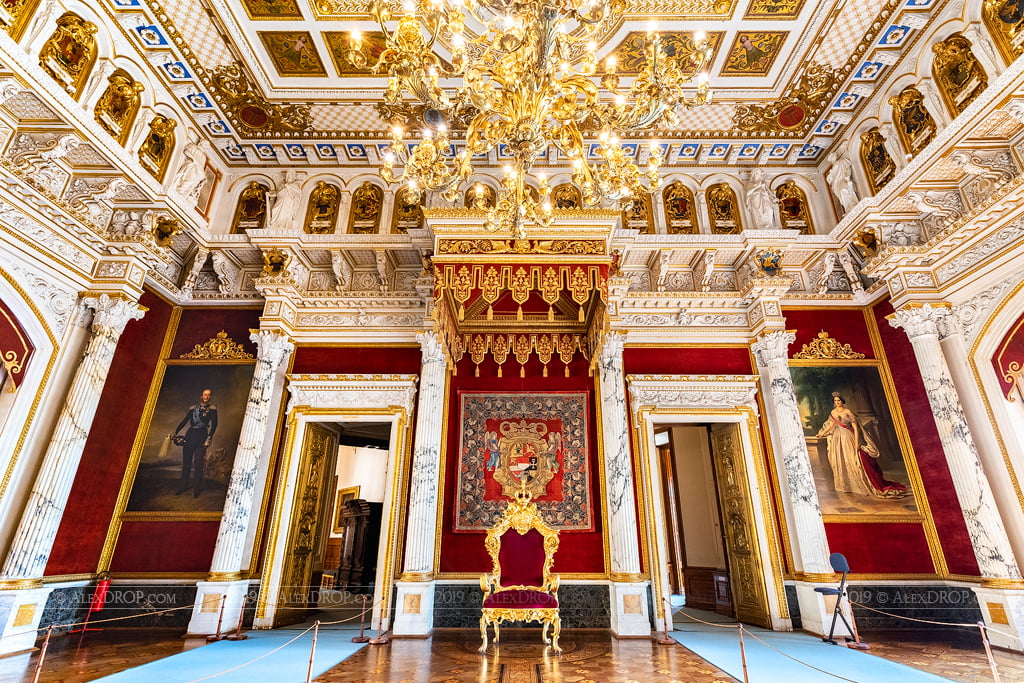 Magnificent Schwerin Castle red and gold accent throne hall interior view with a classy chandelier.
