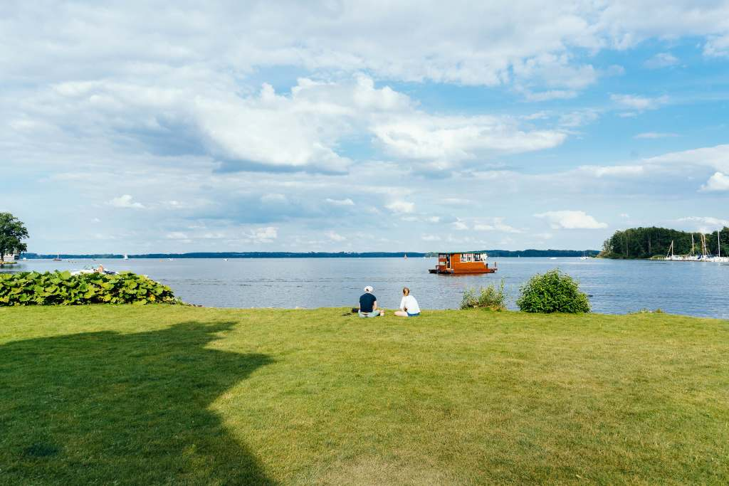 A view of the sprawling grounds surrounding the Schwerin castle near the lake with a boat and two people sitting.