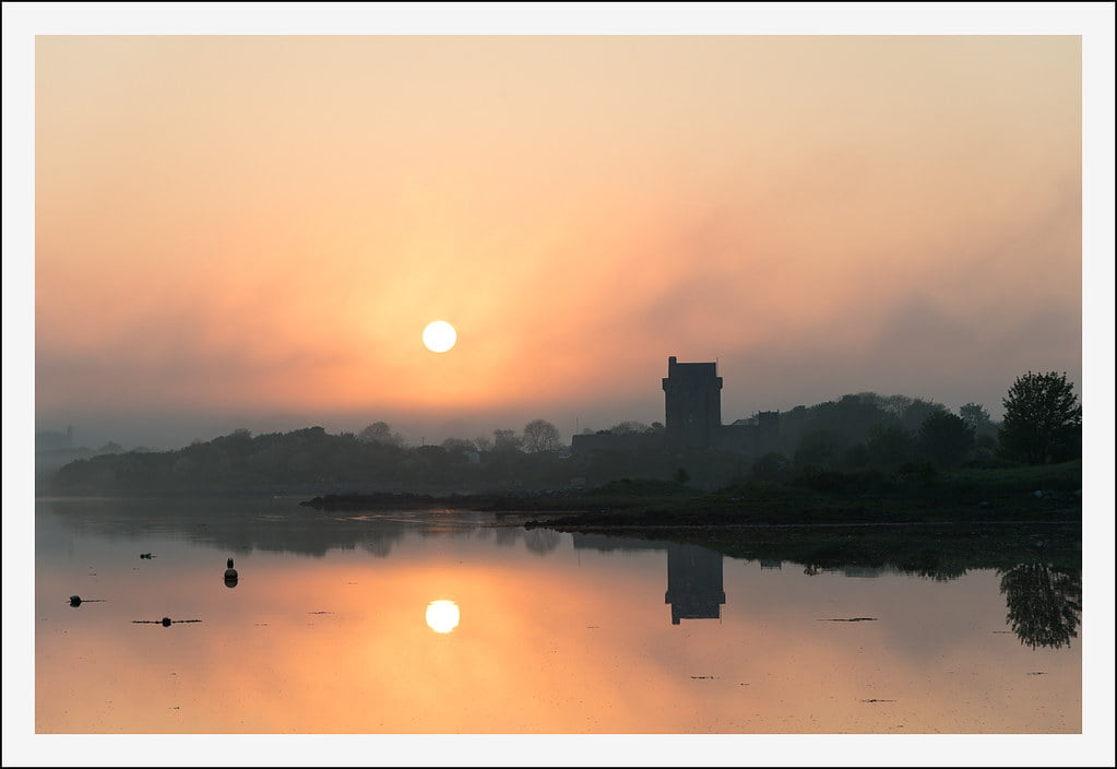 View of the beautiful sunrise at Dunguaire Castle beside the river.