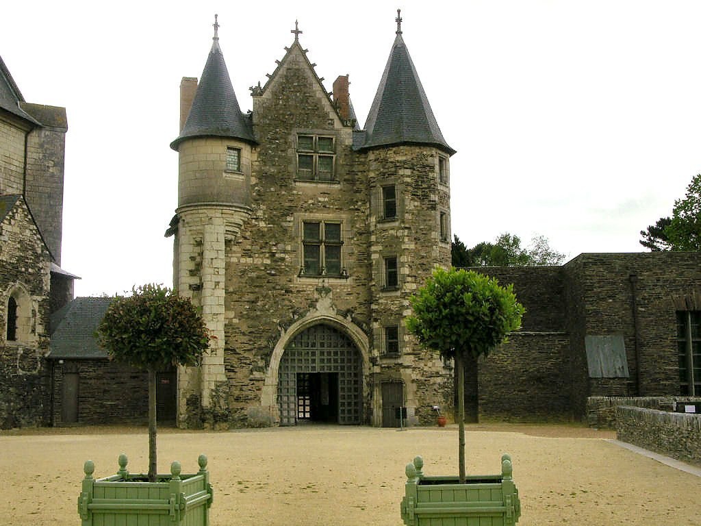 The front gateway of Chateau d'Angers with two trees in the foreground.