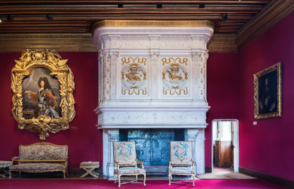 An elegant looking interior inside the Château de Chenonceau with red wallpaper and hanging portraits.
