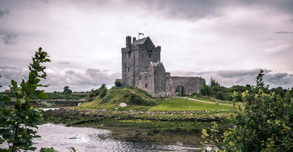 Dunguaire Castle from the other side of the moat with greenery on the sides