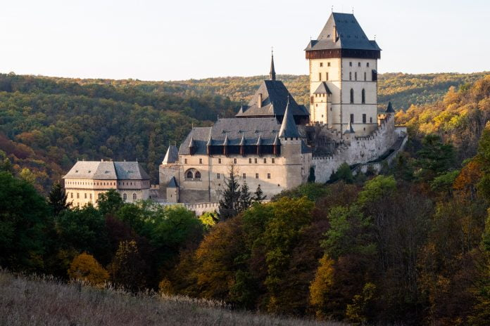Karlštejn Castle's view at the mountain. surrounded by trees.