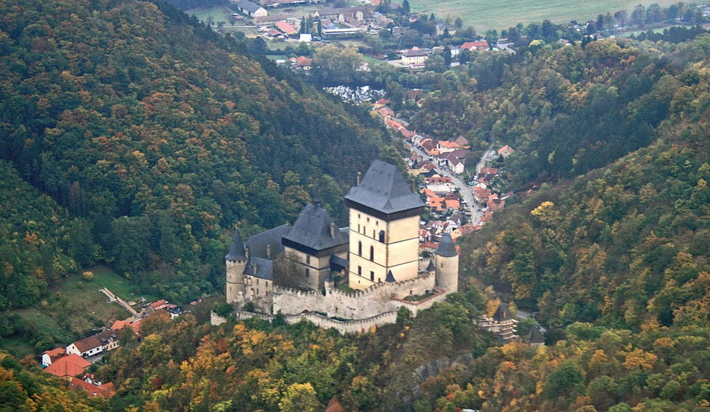 An aerial view of the Karlštejn Castle that highlights its significant geographical position, the road that leads to it, and the town at its base.