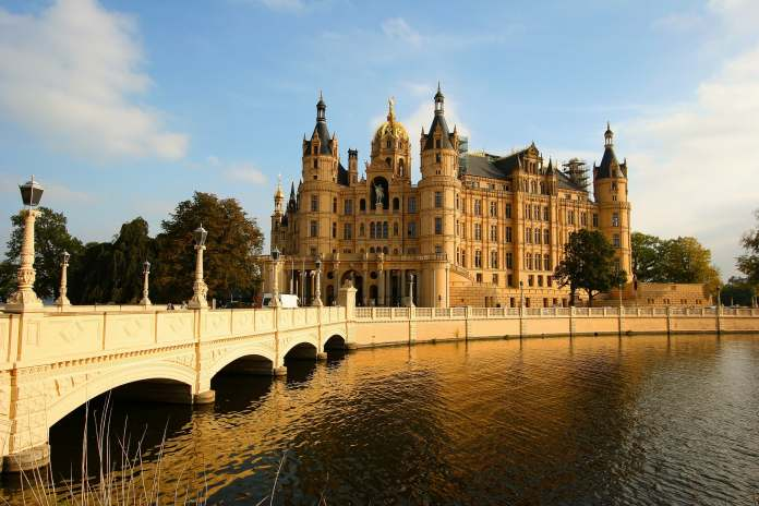 Schwerin Castle perspective before crossing the bridge surrounded by water and sunshine