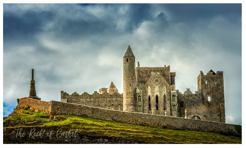 The sideview of Rock of Cashel Castle from a distance with dark clouds in the horizon.