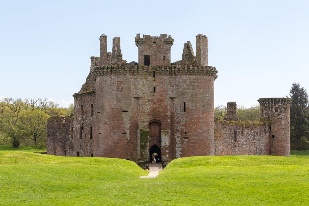 Caerlaverock Castle's entrance surrounded by green grasses.