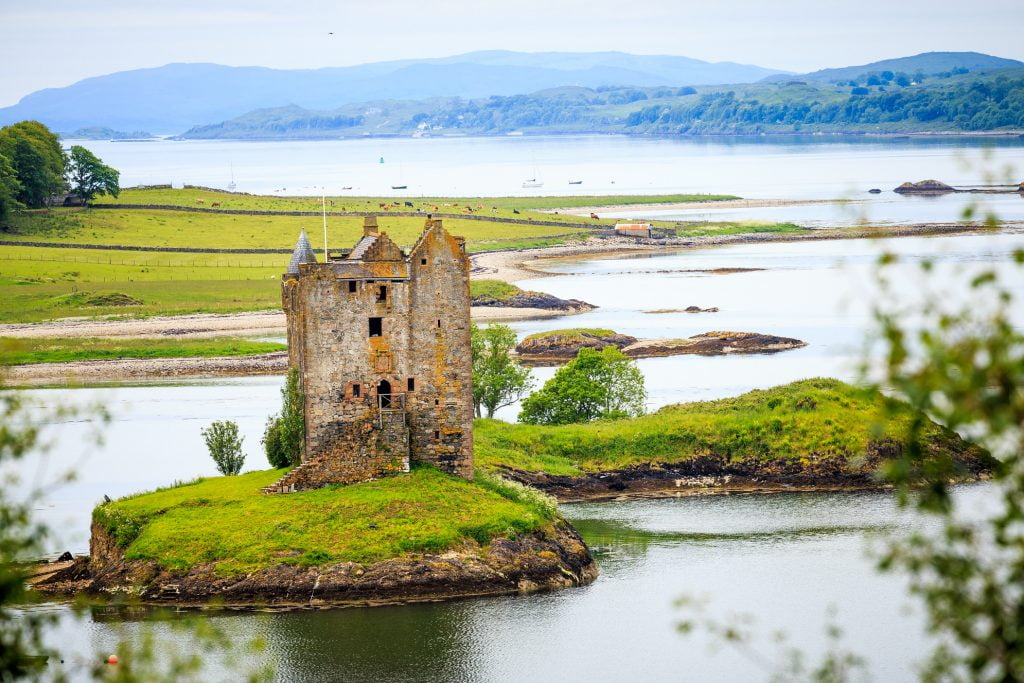 The beautiful shot of Castle Stalker from afar with greenery and water all around.