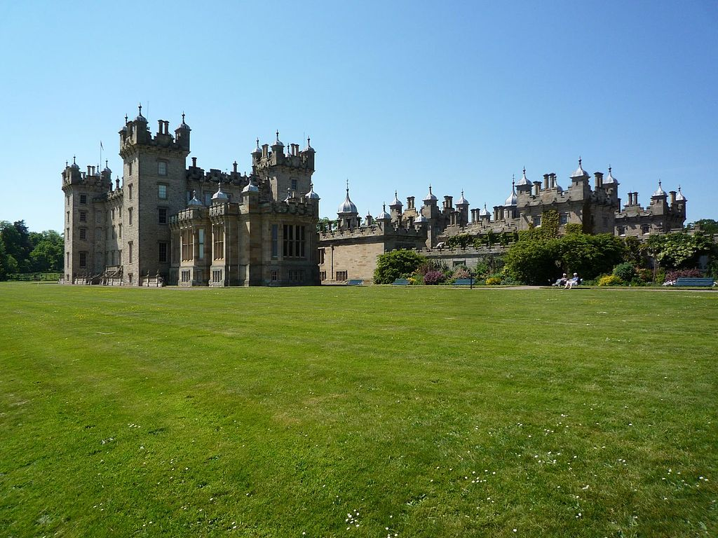 A dramatic view of the castle from across its green grounds .