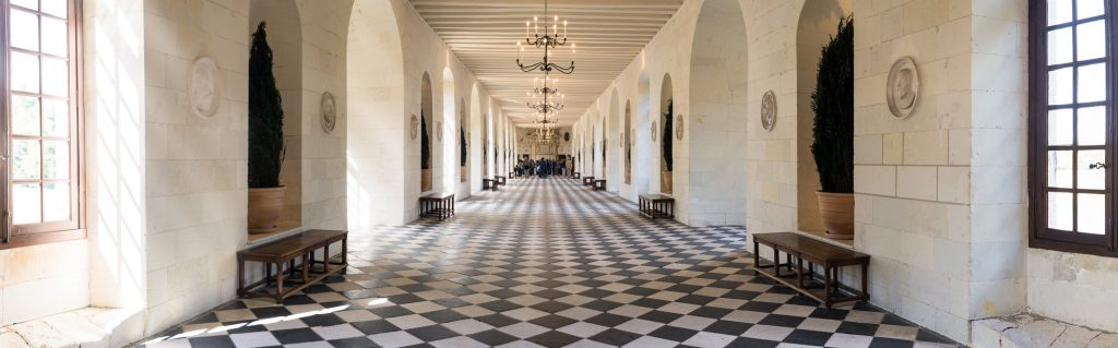 The panoramic view of Château de Chenonceau's hallway interior lined up with chandeliers