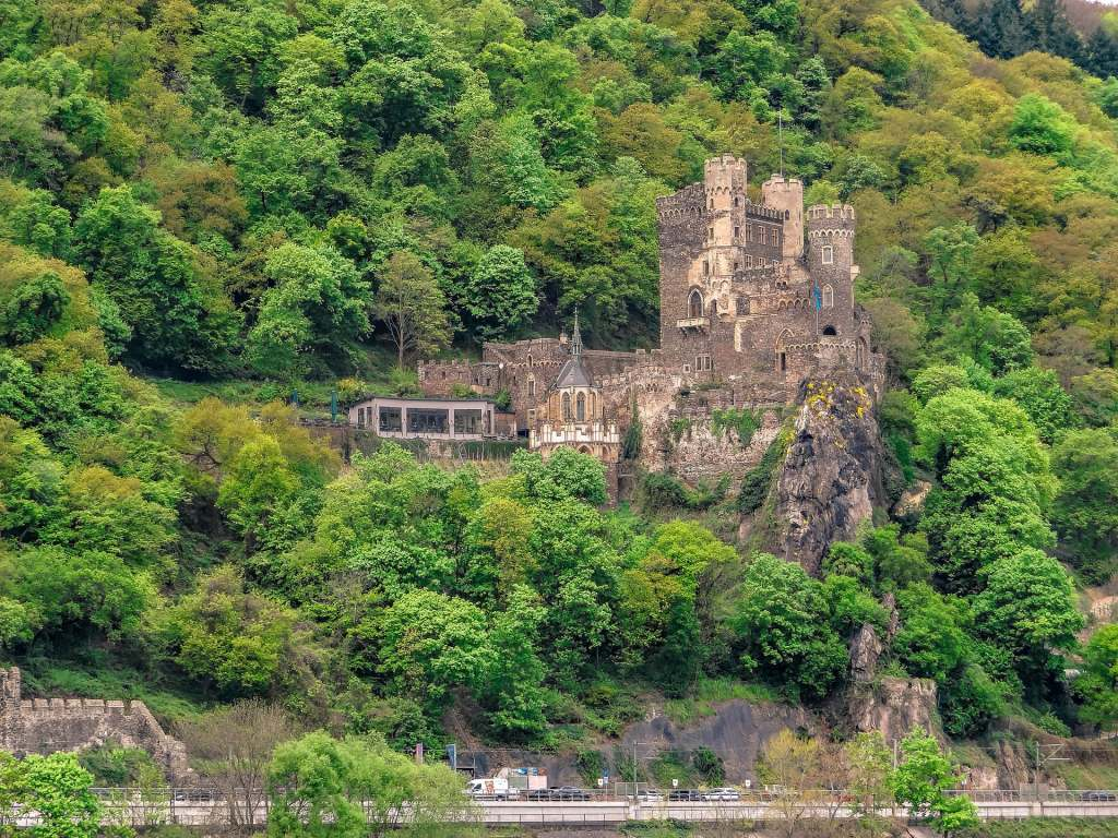 The scenic view of Rheinstein Castle from afar surrounded by greens and the road can be seen from below.