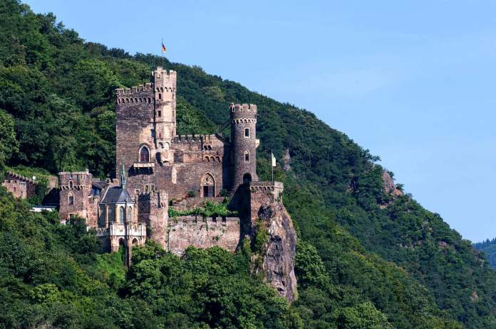 Beautiful view of Rheinstein Castle from afar surrounded by green trees