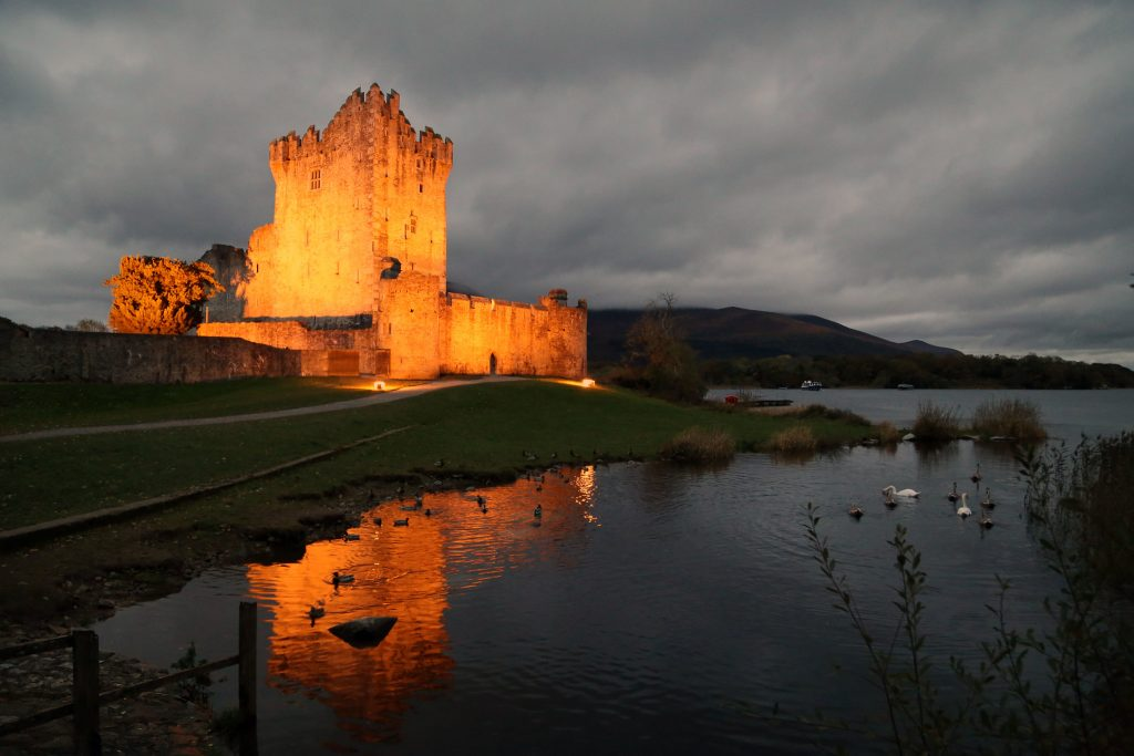 The stunning night view of Ross castle at the lakeside with the lights on.
