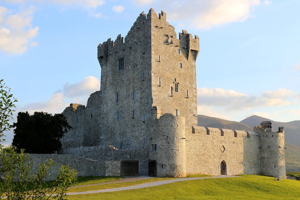 A side view of Ross Castle surrounded by green grass.