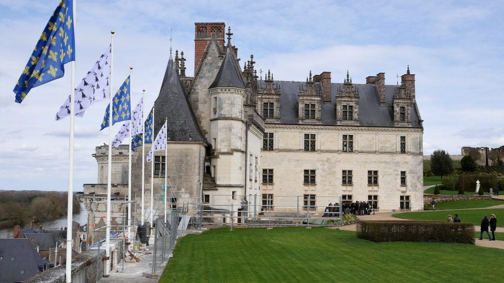 The side structure view of Chateau d'Amboise with the symbolic flag and its green surroundings.