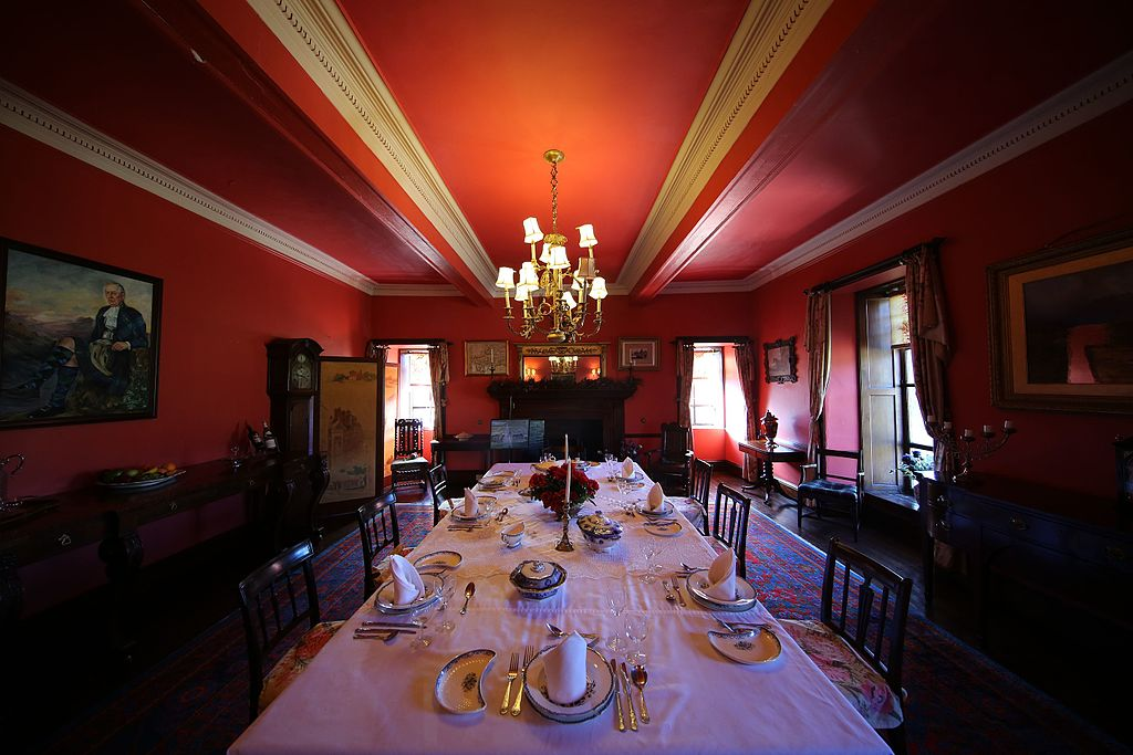 The elegant red dining hall at Braemar's Castle with plates and utensils displayed.