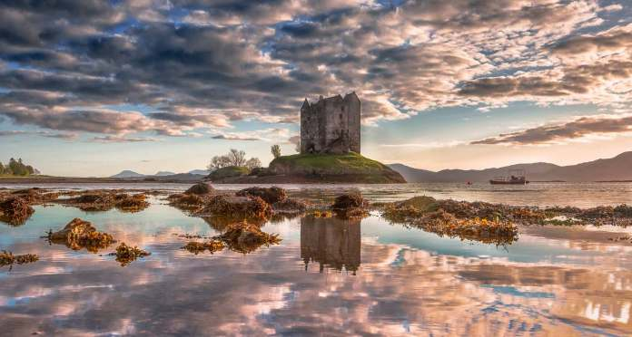 Castle Stalker from afar covered in beautiful pink and golden hues