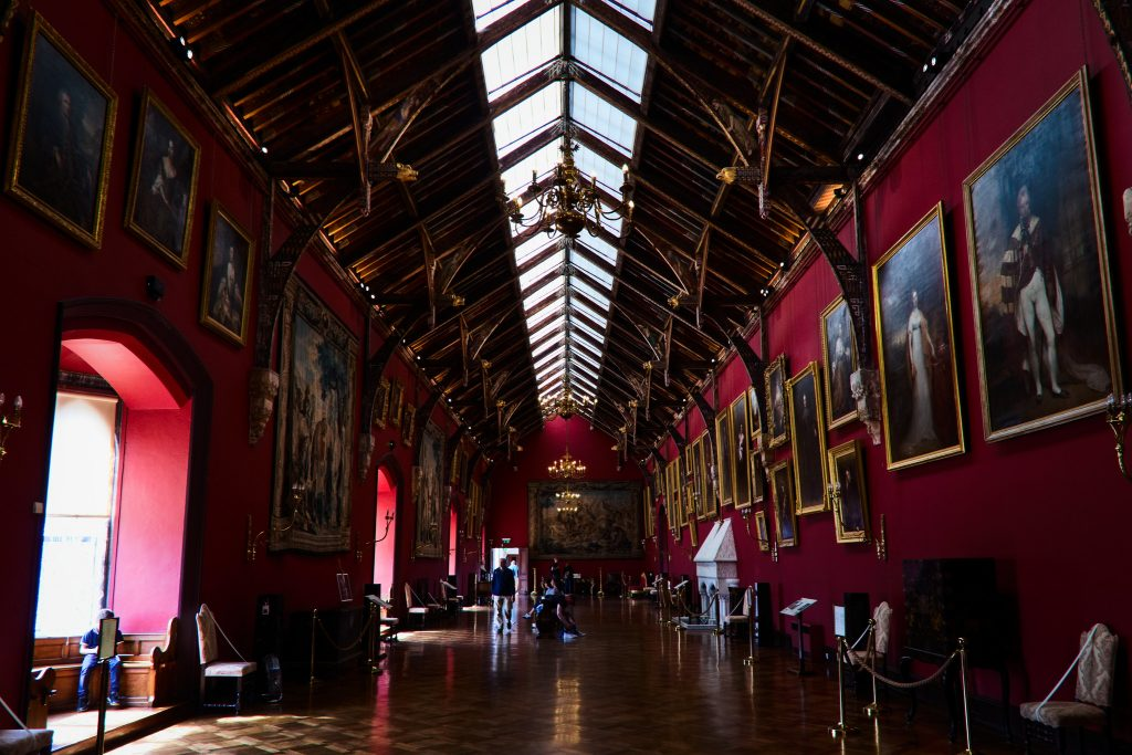 The Red Room inside Kilkenny Castle with portraits displayed.